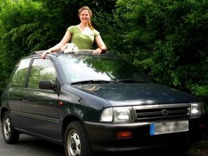 Katrin Herms mit dem Auto-Hund bei offenem Verdeck.