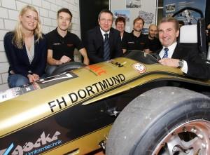 Innovationsminister Pinkwart (hinterm Steuer) war begeistert vom Rennwagen des studentischen Race-Ing.-Teams, hier zusammen mit FH Rektor Wilhelm Schwick (Mitte). Foto:
