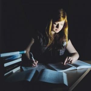 Junge Frau sitzt am Tisch bei Nacht. Vor ihr sind Bücher ausgebreitet. Foto: pflichtlektüre