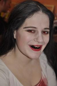 Sandras Lächeln kann doch wirklich entzücken. Mit Hilfe von Zahnschwarz und roten Kontaktlinsen wird aus der netten Studentin das Horrorschneewittchen.
