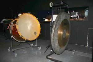 Eine Trommel und ein Gong im Percussion-Raum. Im Hintergrund sieht man den Bildschirm, von dem man die Anweisungen bekommt. Foto: Sabine Knodt