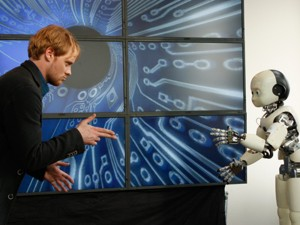 Schauspieler Stefan Konarske spielt Polizeioberkommissar Daniel Kossik. Hier in Interaktion mit einem Roboter der Uni Bielefeld.