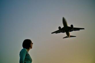 Eine Frau schaut zu einem am Himmel fliegenden Flugzeug auf.