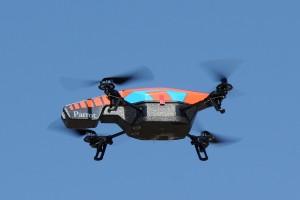 Eine Spielzeug-Drohne fliegt vor einem blauen Himmel.