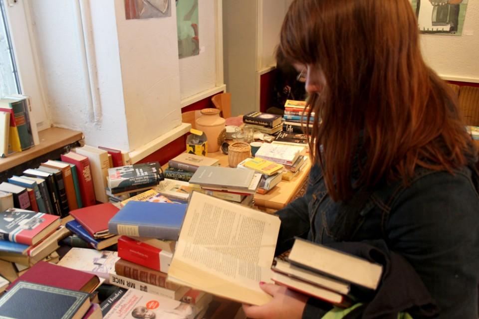 Alina Heine liest in einem Buch, das sie interessiert. Gefällt es ihr, kann sie es einfach mitnehmen. Im Umsonstladen in Dortmund muss niemand auch nur einen Cent bezahlen.
