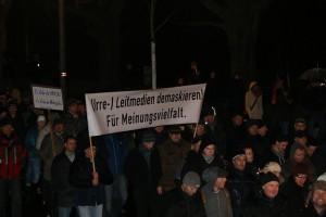 """Demonstranten der Pegida-Bewegung halten ein Plakat mit der Aufschrift """"(Irre) Leitmedien demaskieren! Für Meinungsvielfalt."""""""