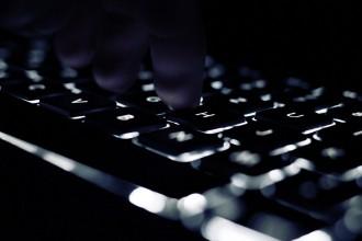 Eine beleuchtete Tastatur im Dunkeln mit einer Hand.