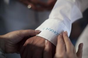 Auf der Modenschau fühlt eine Frau die Punktschriftbestickung auf dem Ärmel eines Mannes.