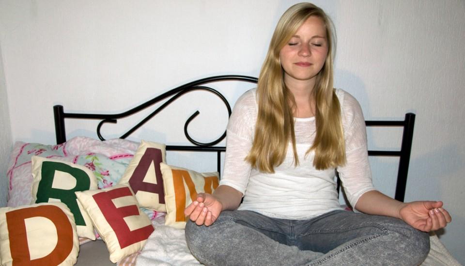 Anja sitzt auf dem Bett und meditiert