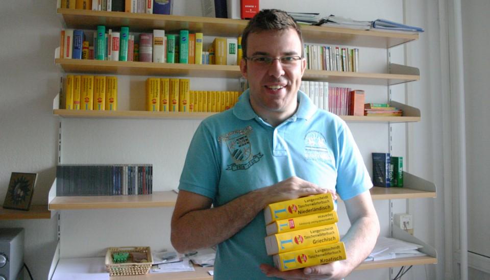 Michal Perlinski mit verschiedenen Wörterbüchern in seinem Wohnheimzimmer.
