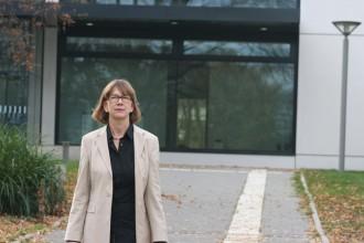 Christa Reicher läuft einen Weg entlang und lächelt.