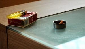 Sein Zigaretten drückt der Mann in einem leeren Teelicht aus.