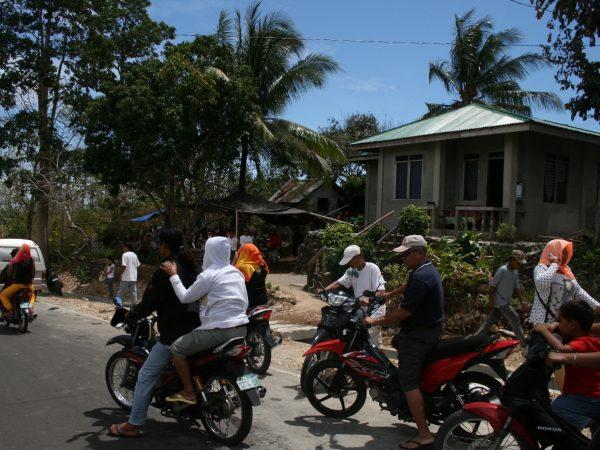 Eine Gruppe aus Rollerfahrern steht auf der Straße.