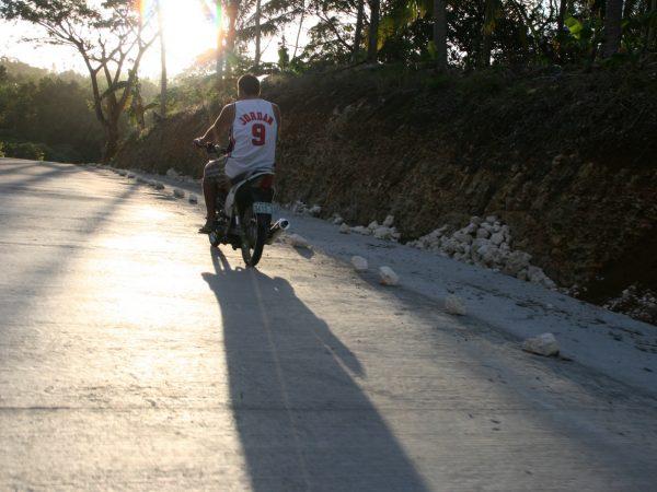 Rollerfahrer fährt in die tief stehende Sonne.