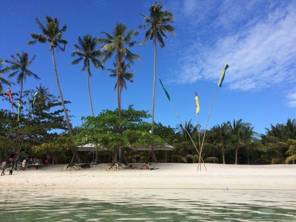 Weißer Sandstrand und Palmen, Blick vom Wasser