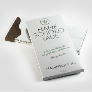 """Man sieht zwei tafeln Schokolade. Sie sind in weißer Folie eingewickelt, auf der ein Hanfblatt draufist und """"hanfschokolade"""" steht."""