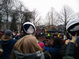Im Vordergrund: Menschen setzen sich weiße Absolventenkappen auf. Im Hintergrund: Eine Studentin hat der Statue die Kappe aufgesetzt und jubelt.