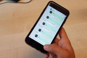 Ein schwarzes iPhone mit einem WhatsApp Chatverlauf wird von einer Hand geladen.