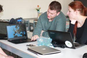 Ein Student und eine Studentin schauen auf einen Laptop, auf dem eine Europakarte und Datenpunkte zu sehen sind.
