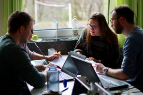 Vier Studenten sitzen mit Laptops an einem Tisch und unterhalten sich angeregt.